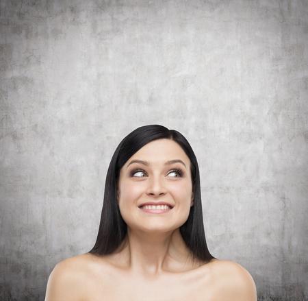 astounded: A portrait of astonishing brunette. Concrete background. Stock Photo