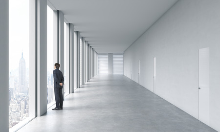 Young professional in formal suit is looking out the window. Empty modern bright clean interior of an open space office. Huge panoramic windows with New York view.