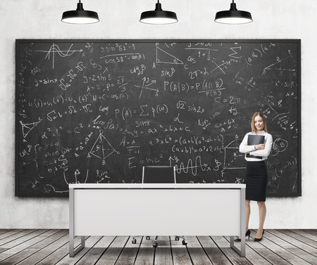 formulae: A beautiful girl presents math calculations on the black chalk board in a modern classroom. Three black ceiling lights, wooden floor and concrete wall. A concept of business education. Stock Photo
