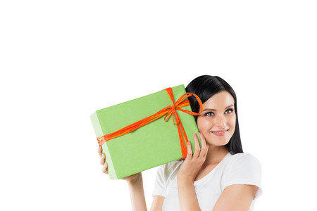 giftwrapped: A smiling brunette is holding a green gift box. Isolated on white background.
