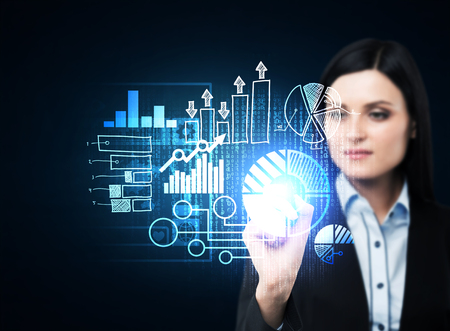 activating: A business woman in formal suit is pushing out the element on the hologram with business icons. Dark background.