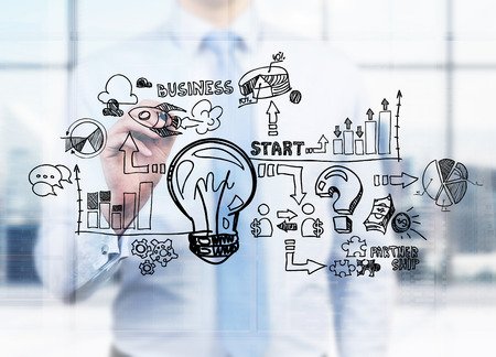 A businessman is drawing a business flowchart on the glass screen. A concept of starting your own business. Stok Fotoğraf