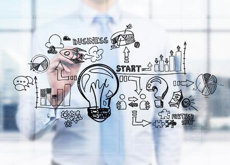 Een zakenman trekt een bedrijfsstroomschema op het glasscherm. Een concept van het starten van een eigen bedrijf. Stockfoto