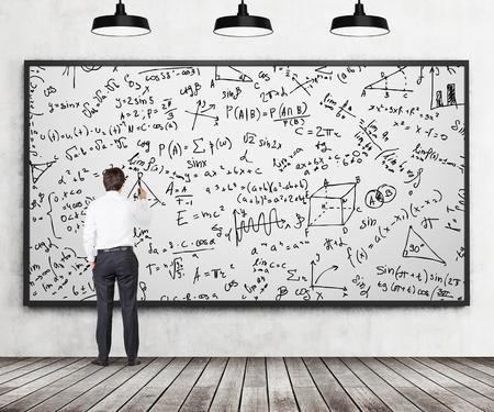数学の数式をホワイト ボードに書いている若い専門家の後姿。解析計算の概念。木製の床、コンクリートの壁、3 つの黒の天井のライトは部屋にい