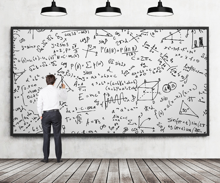 Rear view of young professional who is writing down math formulas on the whiteboard. A concept of analytical calculations. Wooden floor, concrete wall and three black ceiling lights are in the room.