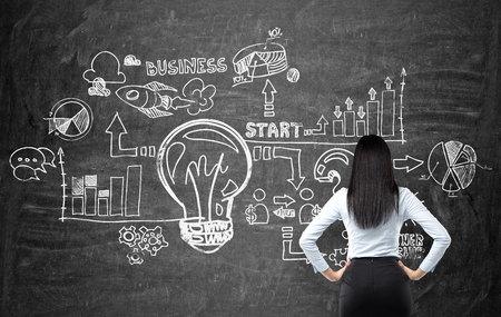 Full length rear view of brunette woman in formal clothes who is looking at the business flowchart on the black chalk board. The concept of business ideas development.