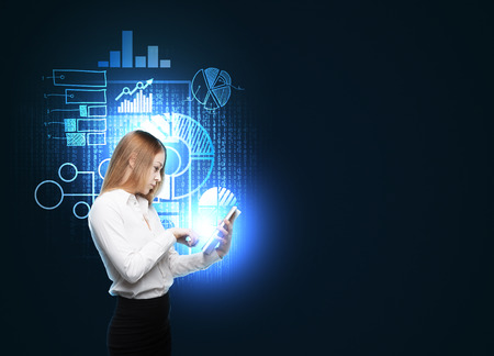 background information: Beautiful woman is browsing some business charts in the tablet. Hologram business charts are flying over the woman. Dark background.