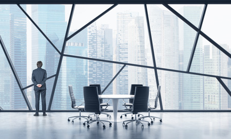 legal services: Rear view of a full length man in a formal suit who is looking out the window in a modern panoramic meeting room in Singapore. The concept of highly professional financial or legal services.