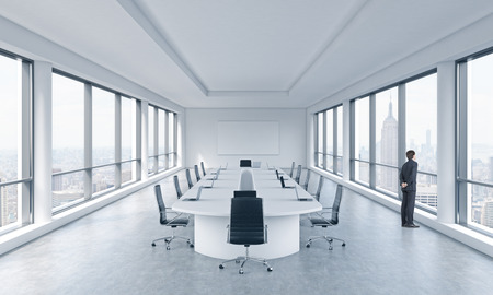 transnational: A Businessman is looking out the window in a modern panoramic meeting room in New York. The concept of the meeting of the Board of Director of the huge transnational corporation. Stock Photo