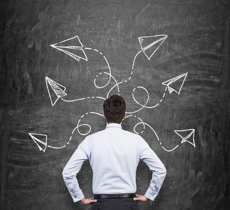 flecha direccion: Vista trasera de un hombre en ropa formal que está reflexionando sobre las posibles soluciones del problema complicado. Muchas flechas con diferentes direcciones se dibujan alrededor de su cabeza en la pizarra negro.