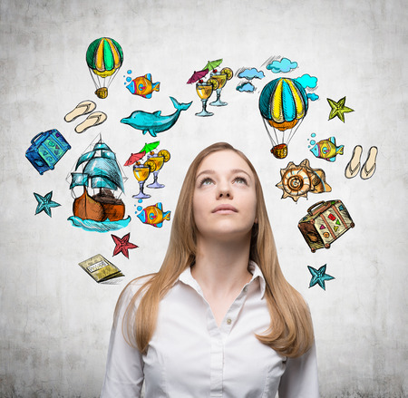 yearning: A beautiful woman is looking up by dreaming about vacation. Colourful vacation icons are drawn on the concrete wall around her head. Stock Photo