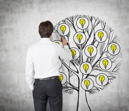 arbol de problemas: Vista trasera de la joven profesional que está dibujando un árbol con las bombillas de luz en la pared de hormigón. Bombillas como un concepto de nuevas ideas de negocio.