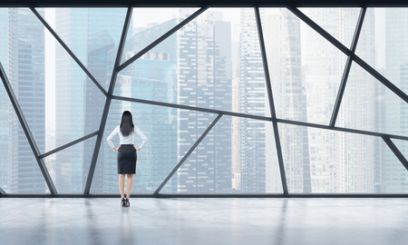 legal services: Rear view of a full length lady in formal clothes who is looking out the window in a modern panoramic open space in Singapore. The concept of highly professional financial or legal services. Stock Photo