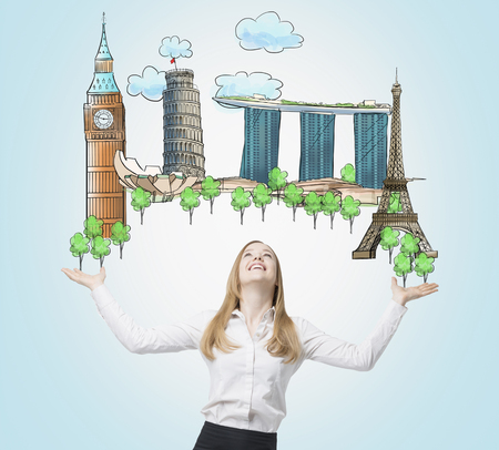 worldwide wish: A beautiful woman is looking up by dreaming about the visiting of the most famous places in the world. The concept of tourism and sightseeing. Light blue background.