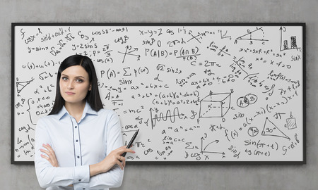 A beautiful brunette is pondering about the solution of complicated analytical problem. Math formulas are written down on the whiteboard. Concrete wall.