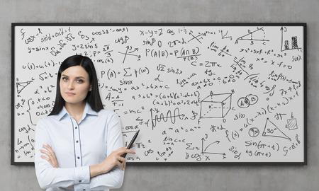 Een mooie brunette is nadenken over de oplossing van complexe analytisch probleem. Wiskundige formules worden afgeschreven op het whiteboard. Betonnen muur. Stockfoto
