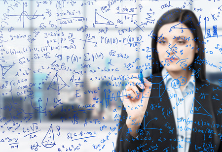 math icon: A brunette woman is writing down math formulas in the glass screen. Modern panoramic office with New York view in blur on the background.