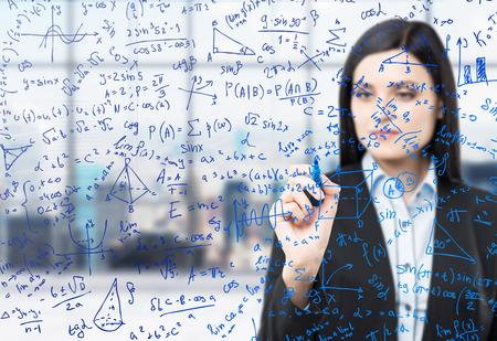 matemáticas: Una mujer morena está escribiendo fórmulas matemáticas en la pantalla de vidrio. Oficina panorámica moderna con vistas de Nueva York en el desenfoque en el fondo.