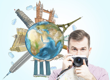 ünlü yer: A handsome tourist with camera and a globe with sketched famous places.