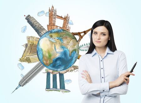 mark pen: A beautiful brunette woman with mark pen and a globe with sketched famous touristic places in the world.