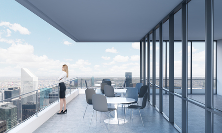 office view: A woman is looking at New York standing on the terrace in a modern skyscraper with panoramic windows. Stock Photo