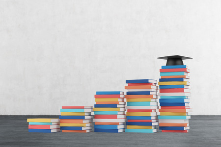 A stair is made of colourful books. A graduation hat is on the final step. Concrete wall and wooden floor.