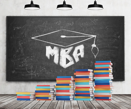 ceiling: A stair is made of colourful books. A graduation hat is drawn on the black chalkboard. MBA concept. Concrete wall, wooden floor and three black ceiling lights.