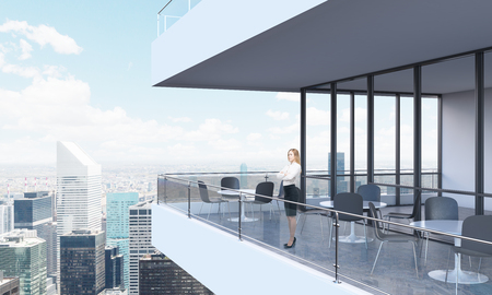 panoramic windows: A woman is looking at New York standing on the terrace in a modern skyscraper with panoramic windows. Stock Photo
