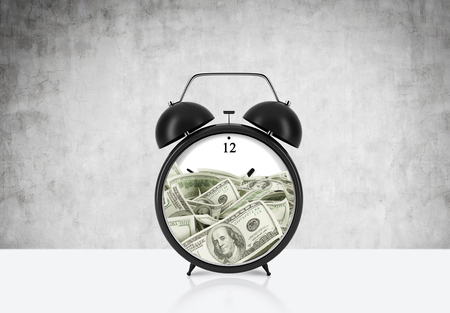 face centered: An alarm clock with dollar bills inside is on the table. The concept of time is money and a time management. Concrete background.