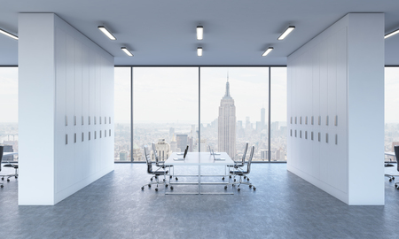 Workplaces in a bright modern open space office. White tables equipped by modern laptops and black chairs. New York panoramic view. 3D rendering.