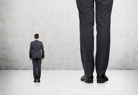 detriment: Rear view of two professionals in formal suites who stand in front of concrete wall.