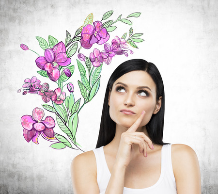 woman looking up: An inspired brunette is dreaming about summer flowers. The sketch of purple flowers is drawn on the concrete wall. Stock Photo