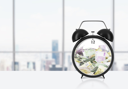 streamlining: There is EURO bills inside the alarm clock which is on the table. The concept of time is money and a time management. Panoramic New York office background. Stock Photo