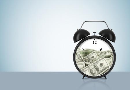 dollaro: Una sveglia con il dollaro all'interno � sul tavolo. Il concetto di 'tempo � denaro' e una gestione del tempo. Sfondo azzurro. Archivio Fotografico