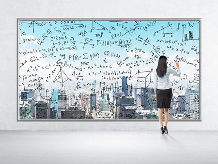formulae: Rear view of business lady who is drawing math formulas on the New York panoramic poster. A room with concrete wall and floor.