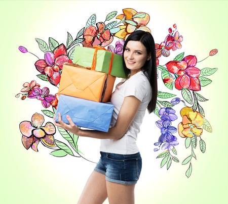 light green wall: A smiling brunette holds colourful gift boxes. The sketch of different flowers is drawn on the light green wall. Stock Photo
