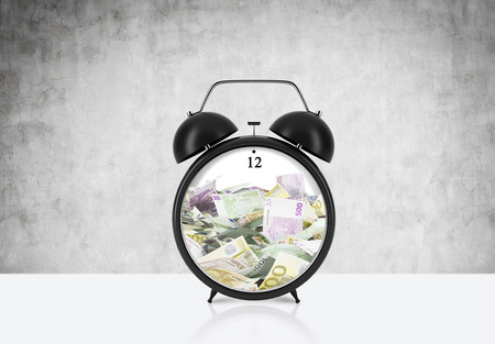 centred: There is EURO bills inside the alarm clock which is on the table. The concept of time is money and a time management. Concrete background.
