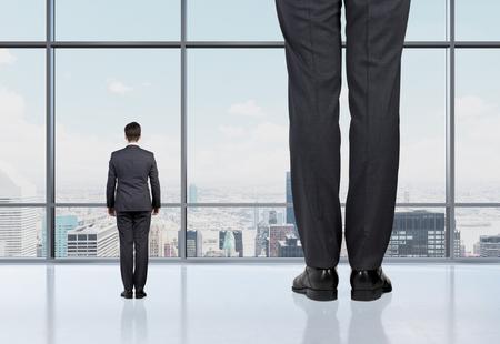 Achter mening van twee professionals in formele suites die in de voorkant van een panoramisch raam met New York uitzicht op de stad staan. Het concept van de professionele adviesdiensten.