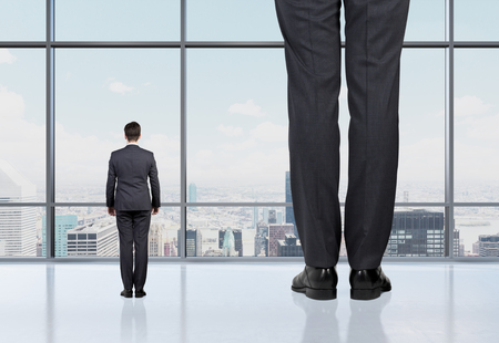 men standing: Rear view of two professionals in formal suites who stand in front of panoramic window with New York city view. The concept of professional consulting services.