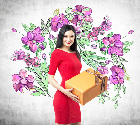 giftwrapped: A smiling brunette in a red dress holds an orange gift box. The sketch of purple flowers is drawn on the concrete wall.