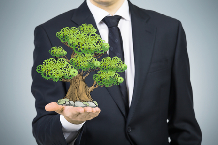 Een persoon in formele pak heeft een geschetste boom op de handpalm. Lichtgrijze achtergrond. Een concept van de business development. Stockfoto