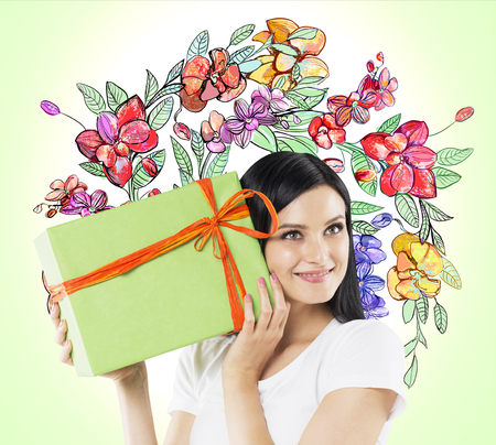 light green wall: A curious brunette woman tries to guess what is inside the green gift box. The sketch of colourful flowers is drawn on light green wall.