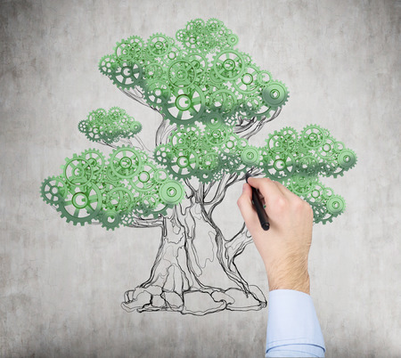 innovator: A hand is drawing a tree on the concrete wall. A concept of the process of a growing business or a start up.