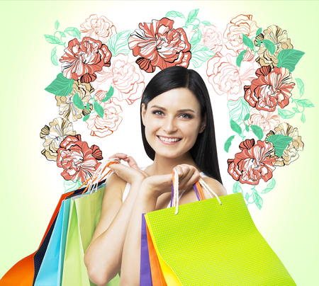 light green wall: A smiling brunette woman holds colourful bags from fancy shops. The concept of shopping. A sketch of different flowers is drawn on the light green wall.