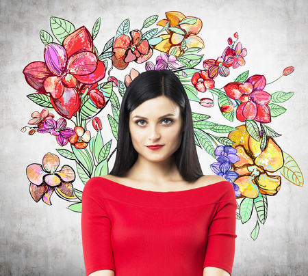 demure: A portrait of a pensive brunette in a red dress. The sketch of different flowers is drawn on the concrete wall.