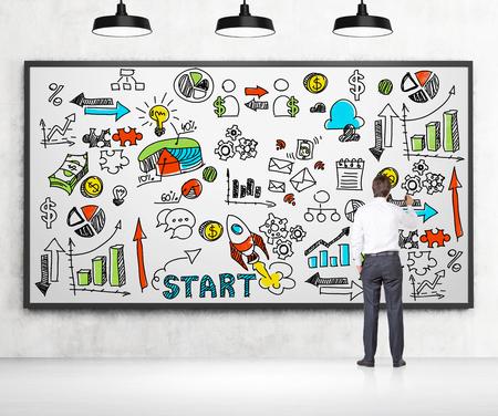 Een zakenman in formele kleding is het tekenen van een kleurrijke zakelijke grafieken en pictogrammen op het witte bord. Een concept van het starten van een nieuw bedrijf. Er zijn betonnen muur en drie zwarte plafondlampen. Stockfoto