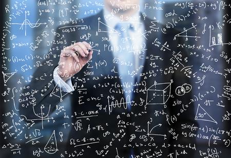 napsat: Podnikatel píše dolů matematické vzorce na skleněnou zástěnou ve večerním moderní panoramatické kanceláře.