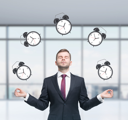 meditative: Meditative businessman is pondering about time management in the modern panoramic office. The person in formal suit is surrounded by alarm clocks. A concept of time management and deadlines.