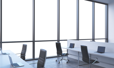 company premises: Workplaces in a bright modern open space office. White tables equipped with modern laptops and black chairs. White copy space in the panoramic windows. 3D rendering. Stock Photo