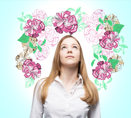 encircling: An inspired woman is dreaming about summer flowers. The sketch of purple flowers is drawn on the light blue wall.